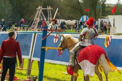 Un chevalier sur le cheval frappe l'anneau de cible photos libres de droits