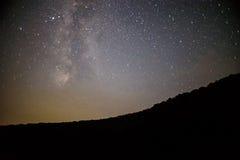 Un chiaro cielo notturno con una collina ed alberi nella priorità alta Fotografie Stock Libere da Diritti