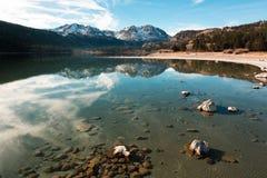 Un chiaro lago alpino un giorno soleggiato fotografie stock