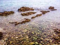 Un chiaro mare che copre le rocce variopinte immagini stock
