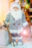 Un chiffre de Santa Claus dans des vêtements gris avec une lampe-torche dans sa main sous l'arbre de nouvelle année Image stock
