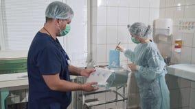 Un chirurgo femminile prende una vestaglia sterile dal pacchetto Un gruppo di medici nelle maschere sta preparando per archivi video