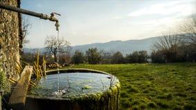 Un chorrito del agua cae en una tina redonda vieja de la piedra cubierta de musgo fotos de archivo