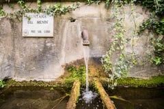 Un chorrito del agua cae en una tina redonda vieja de la piedra cubierta de musgo imagenes de archivo