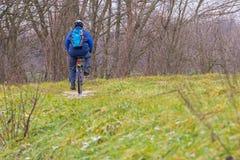 Un ciclista con una mochila va abajo del camino del campo Imagen de archivo