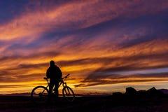 Un ciclista contro un bello tramonto Un uomo sta con una bicicletta ed esamina il tramonto fotografia stock