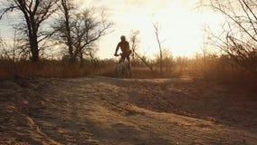 Un ciclista dell'uomo guida un mountain bike su una strada non asfaltata, strada rurale in un campo al tramonto in freddo Incroci video d archivio
