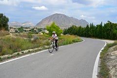 Un ciclista en las montañas con paisaje imponente Fotos de archivo