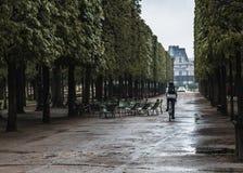 Un ciclista guida attraverso il parco a Parigi dopo la pioggia fotografia stock