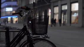 Un ciclista guida attraverso la città con la torcia elettrica inclusa Bicicletta con un canestro stock footage