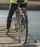 Un ciclista monta un puente de madera en una bicicleta imagenes de archivo