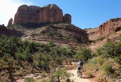 Un ciclista in mountain-bike guida verso la roccia famosa della cattedrale del ` s di Sedona Fotografie Stock Libere da Diritti