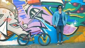 Un ciclista que se inclina en una pared coloreada Adolescente masculino caucásico elegante joven almacen de metraje de vídeo