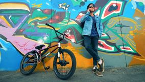 Un ciclista se coloca que habla en un teléfono El hombre joven se coloca con una bici, habla en un teléfono móvil almacen de video