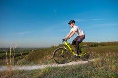 Un ciclista in una maglia con cappuccio arancio guida una bici lungo un percorso della montagna Il concetto degli sport estremi immagini stock libere da diritti