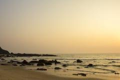 Un ciel clair gris de coucher du soleil de rose au-dessus de la mer contre une plage sablonneuse avec des roches dans l'océan image stock