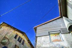 Un ciel complètement des étoiles entre de vieilles maisons Images stock