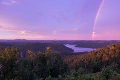 Un cielo coloreado púrpura con un arco iris en la puesta del sol sobre el lago mountain Foto de archivo libre de regalías
