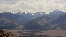Un cielo del día del lapso de tiempo sobre las montañas con los picos nevosos almacen de video