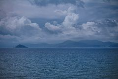 Un cielo densamente nuvoloso con le nuvole di tempesta Vista panoramica delle montagne sull'isola a distanza fotografie stock
