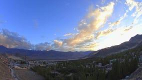 Un cielo variopinto di tramonto delle nuvole di lasso di tempo sopra una città in una valle della montagna stock footage