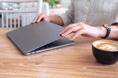 Un cierre de la mujer y abrir un ordenador portátil en la tabla después de acabado el usar de ella fotos de archivo libres de regalías
