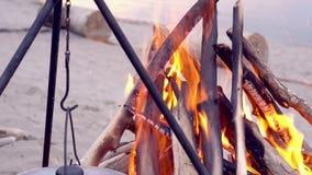 Un cierre del fuego para arriba en la playa de la tarde por el mar En un fuego la comida en un cobre se cocina almacen de video