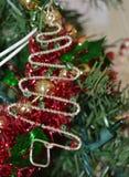 Un cierre encima de la foto de un ornamento doblado, viejo del árbol de navidad en un árbol de navidad Foto de archivo libre de regalías
