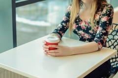 Un cierre encima de la foto de una mujer encantadora que se sienta en la tabla en un café cerca de ventana y del café caliente de Fotos de archivo libres de regalías