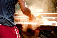 Hombre que usa la amoladora de madera. Imagen de archivo