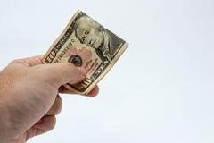 Un cierre encima de la imagen de una mano masculina caucásica que lleva a cabo una nota de diez dólares con un fondo llano imagenes de archivo