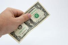 Un cierre encima de la imagen de una mano masculina caucásica que lleva a cabo una nota de un DollarUSA con un fondo llano imagen de archivo libre de regalías