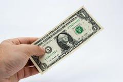 Un cierre encima de la imagen de una mano masculina caucásica que lleva a cabo una nota de un DollarUSA con un fondo llano imagen de archivo