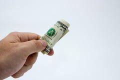 Un cierre encima de la imagen de una mano masculina caucásica que lleva a cabo una nota de un DollarUSA con un fondo llano foto de archivo libre de regalías