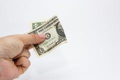 Un cierre encima de la imagen de una mano masculina caucásica que lleva a cabo una nota de un DollarUSA con un fondo llano foto de archivo