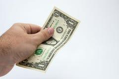 Un cierre encima de la imagen de una mano masculina caucásica que lleva a cabo una nota de un DollarUSA con un fondo llano fotografía de archivo libre de regalías