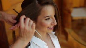 Un cierre encima de la opinión un profesional que hace un peinado de la boda para una novia joven hermosa La mañana del ` s de la almacen de metraje de vídeo