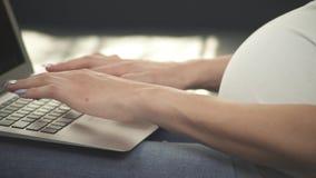 Un cierre encima de la vista lateral de las manos embarazadas de los woman's que mecanografían en el teclado de los ordenadores almacen de metraje de vídeo