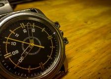 Un cierre encima del reloj análogo de metálico de plata con el fondo de madera foto de archivo libre de regalías