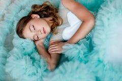 Un cierre encima del retrato de una chica joven hermosa con los ojos azules, compone y peinado en una mentira enorme del vestido  foto de archivo