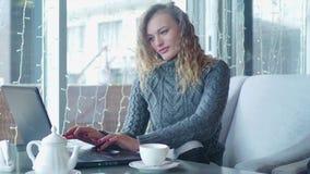 Un cierre encima del tiro de una mano de la mujer que mecanografía usando la tableta en la cafetería almacen de metraje de vídeo