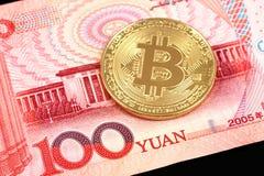 Un cierre físico del bitcoin para arriba con una nota china de 100 Yuan Imagenes de archivo