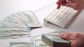 Un cierre para arriba de las manos masculinas que cuentan al hombre de los billetes de banco del dólar de EE. UU. está contando e almacen de video