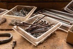 Un cierre para arriba de un surtido de clavos y de tornillos en un banco de trabajo de madera, luz natural foto de archivo libre de regalías