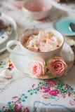 Un cierre para arriba de una taza con el té adornado con las rosas foto de archivo