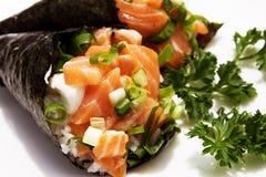Un cierre para arriba del temaki de color salmón contra un fondo blanco Foto de archivo