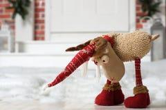 Un ciervo del juguete en una capilla roja se coloca en la nieve cerca de la puerta de la casa Imagenes de archivo