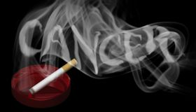 Un cigarrillo ardiente en un cenicero rojo Imagen de archivo