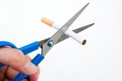 Un cigarrillo del corte de la mano Foto de archivo libre de regalías