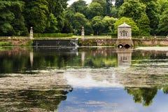 Un cigno, un arco ed acque romantiche su una proprietà inglese Fotografia Stock Libera da Diritti